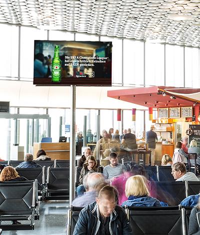 Programmatisch ausgespielte Heineken-Werbung in der Abflughalle eines großen Flughafens
